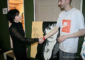 Enya signing a painting for the World Music Awards charity, London, 2006